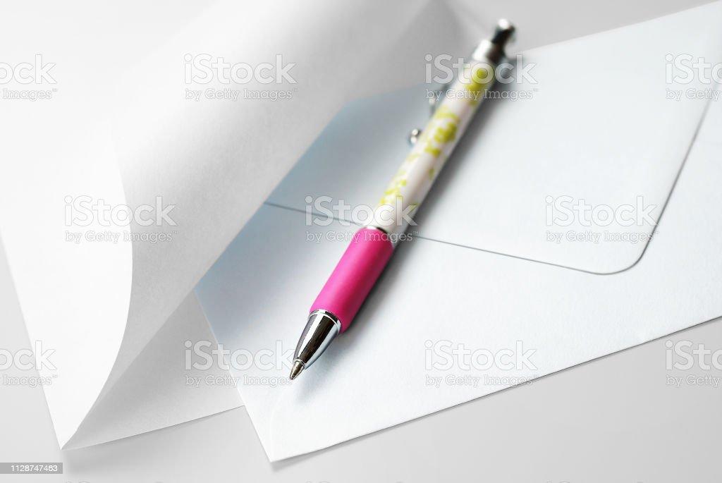 Jeu de correspondance: Feuille blanche avec coin recourbé, enveloppe et stylo - Photo