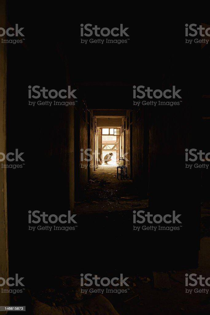 Corridoio e Silhouette di un uomo Accovacciarsi in foto stock royalty-free