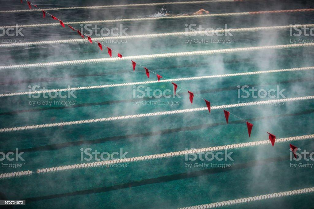 Carriles del corredor y banderas en piscina con agua limpia. Niebla sobre el agua. Deporte de competición - foto de stock