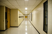 Corridor of a school with neon light on ceiling and a door at the other end