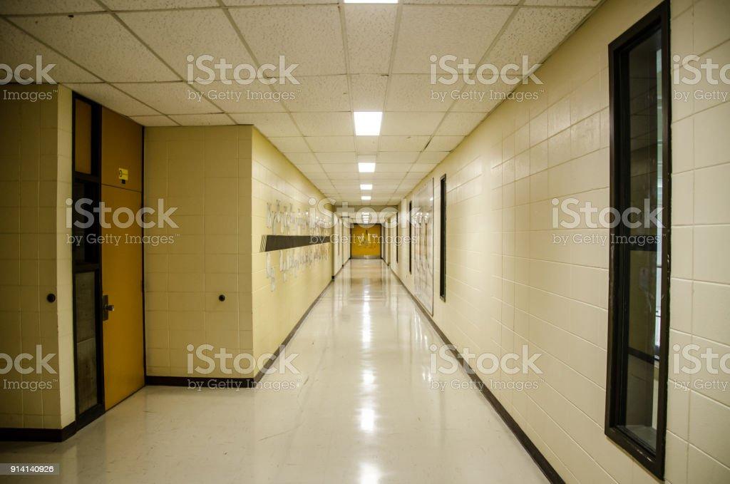 Korridor einer Schule mit Neonlicht an Decke und eine Tür am anderen Ende – Foto