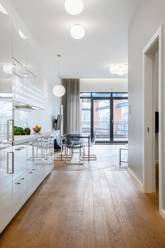 Corridor with wooden floor to white furniture kitchen with modern dining area and window doors to balcony