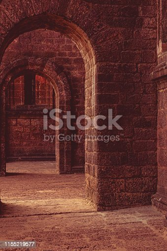 Corridor with arches outside an old church. Walls and pillars made of red brick sand stone.