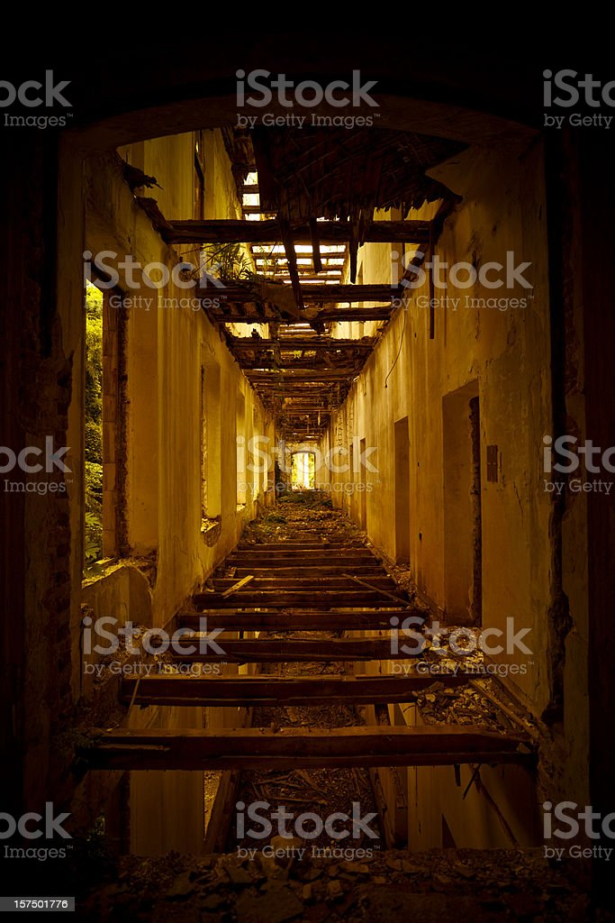 Corridor with broken floor and ceiling in abandoned house royalty-free stock photo