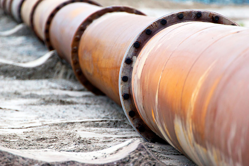 Corroded pipelines, used for land reclamation, on a beach. Holland
