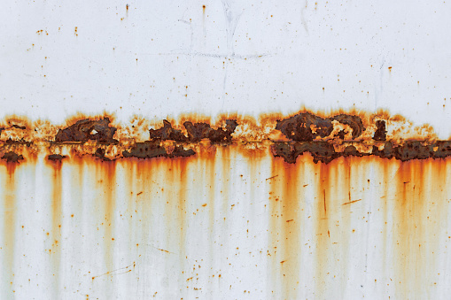 Corrosion of welding seam with red stains on a old white metal sheet. Abstract background