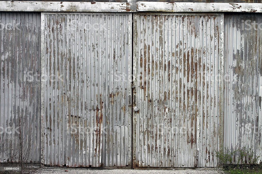 Corrugated door at abandoned factory building stock photo