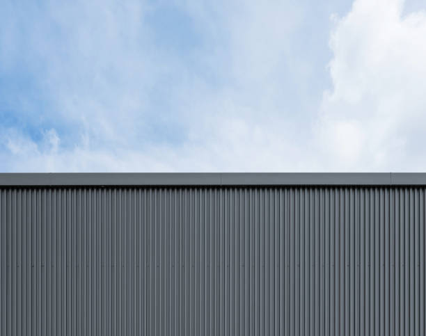 wellblechfabrik industriewand auf blauem himmel mit wolken - alu zaun stock-fotos und bilder