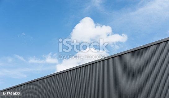 istock Corrugated factory industry wall on blue sky with clouds 643791622