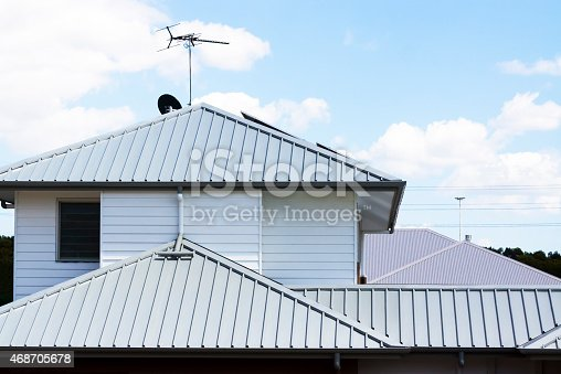 Modern corrugated iron roofs with tv antenna and satellite dish against sky with white clouds, full frame horizontal composition