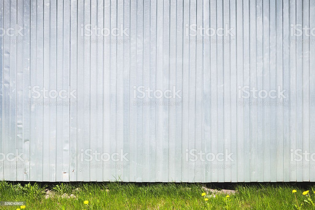 Corrugado de metal valla se encuentra en césped verde foto de stock libre de derechos