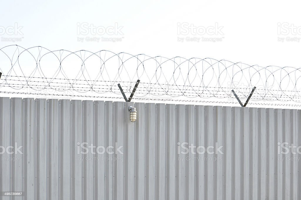 Corrugated metal sheet fence with barbed wires on top stock photo