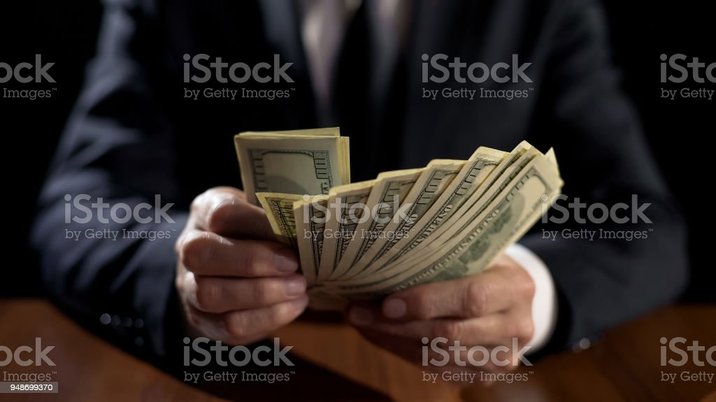 Corrupt official holding bundle of money, taking bribe for abuse of power royalty-free stock photo