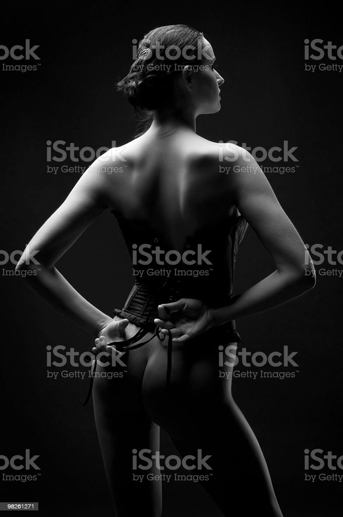 Corseted woman in the dark royalty-free stock photo