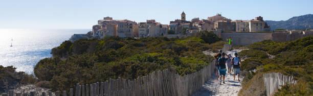 corse: une clôture en bois et passants devant les toits de la vieille ville de bonifacio, la ville à la pointe sud de l'île - randonnée corse photos et images de collection