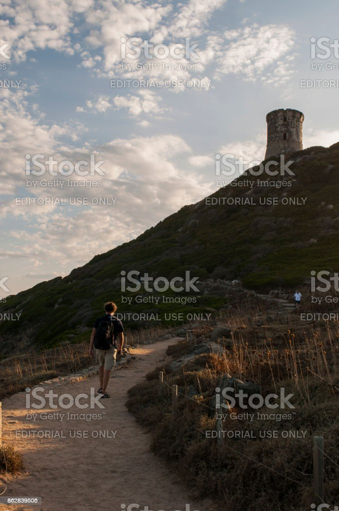 Corsica: man walking at sunset on the panoramic footpath to La Parata Tower, a ruined Genoese tower built in 1608 in front of the Iles Sanguinaires, the Bloody Islands stock photo