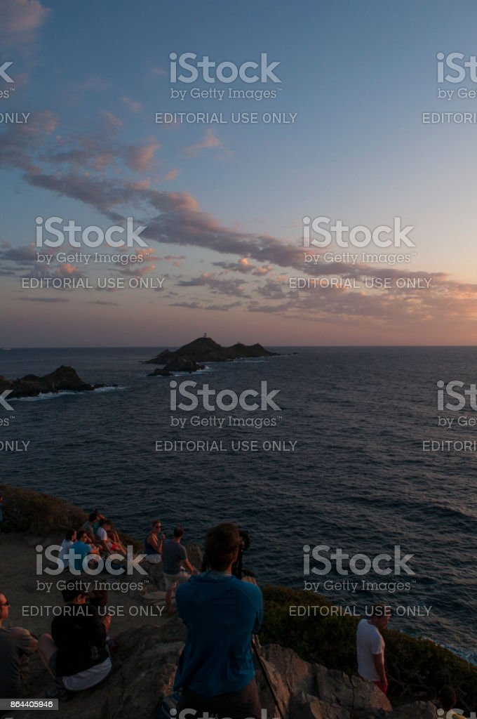 Corsica: people looking at sunset on the Iles Sanguinaires (Bloody Islands) with a lighthouse dating 1844 stock photo