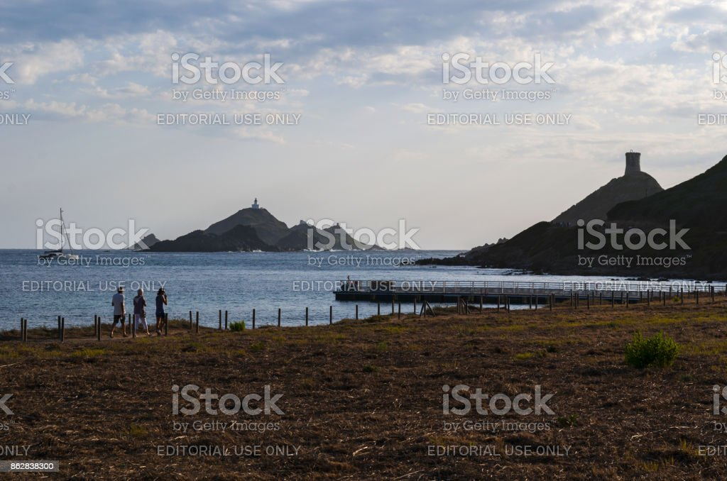 Corsica: people walking at sunset on the panoramic footpath to La Parata Tower, a ruined Genoese tower built in 1608 in front of the Iles Sanguinaires, the Bloody Islands stock photo
