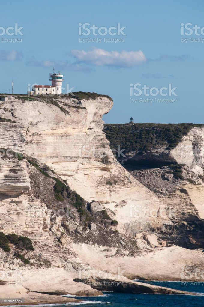 Corsica: the breathtaking white limestone cliffs of Bonifacio in the International Bouches de Bonifacio marine park, nature reserve established in 1993, with view of the Cape Pertusato Lighthouse stock photo