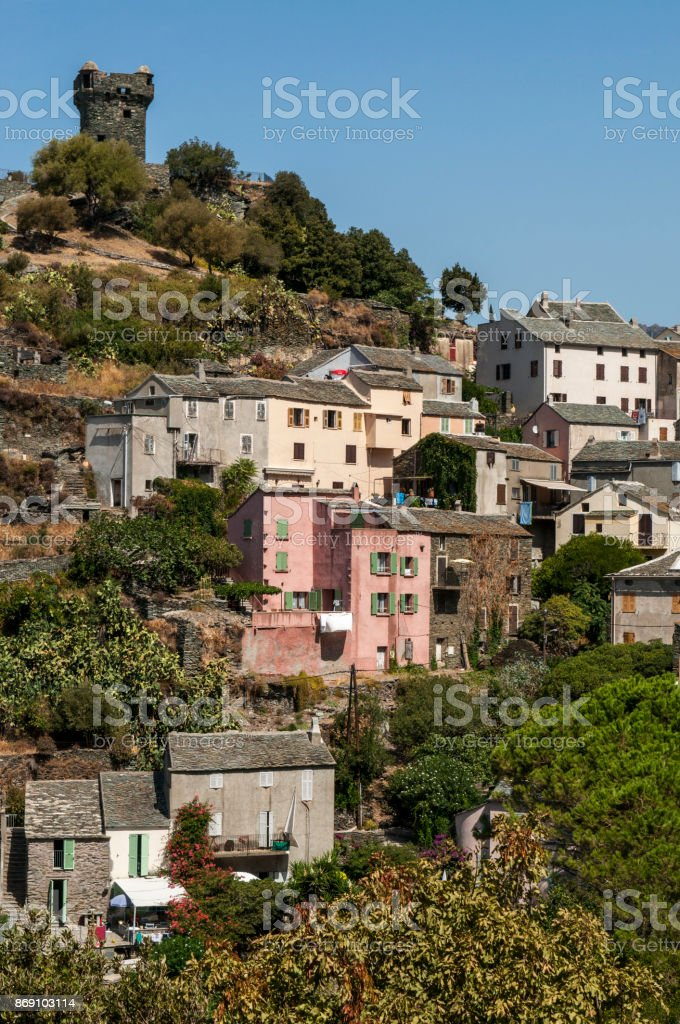 Corsica: the skyline of Nonza, village on the western coast of Cap Corse with ancient houses perched on sheer cliffs atop 100 metres to the sea below and its Genoese tower (16th century) stock photo