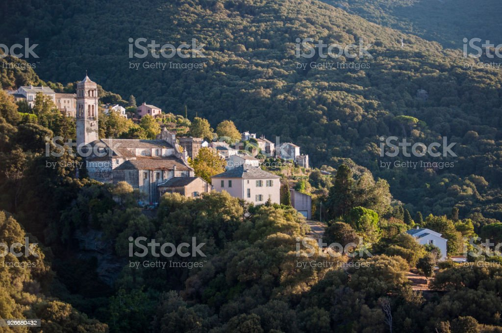 Corsica:the Mediterranean maquis with view of the skyline of one of the remote villages of the Haute Corse on the western side of Cap Corse, famous for wild landscapes stock photo