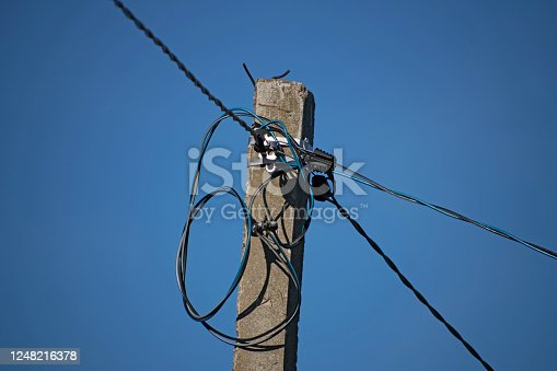 Coseup of old electricity pole, wire, Electricity power pole. A convoluted mess of wires and cables clutter.