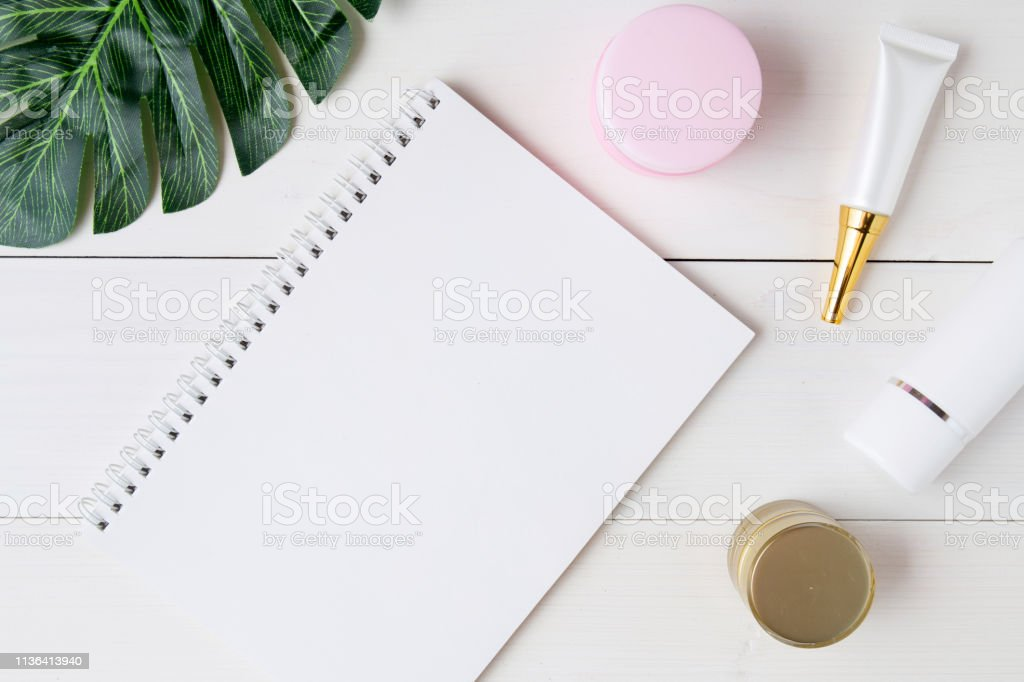 cosmetic and skin care product and notebook and leaves on table,...