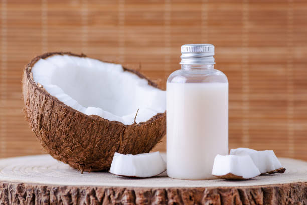 cosmetic bottle and fresh organic coconut for skincare, natural background stock photo