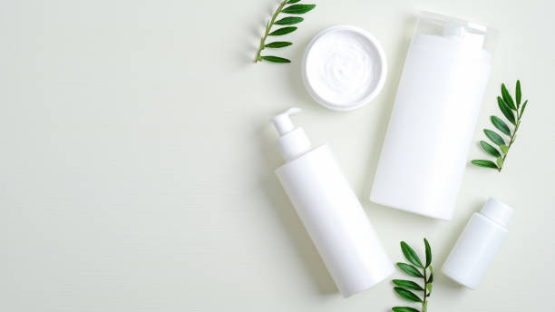 SPA cosmetic bottle containers and cream jar with green leaves. Minimalist cosmetic product mockups, natural branding. Organic beauty cosmetics for SPA treatment