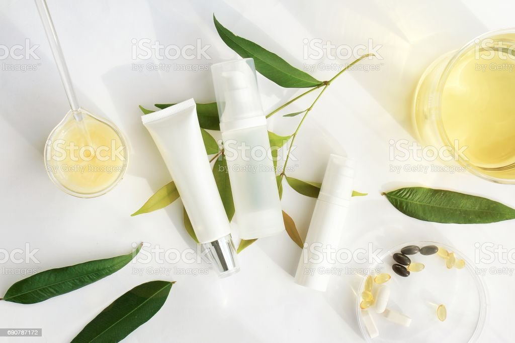 Cosmetic bottle containers with green herbal leaves, Blank label for branding mock-up, Natural beauty product concept. stock photo