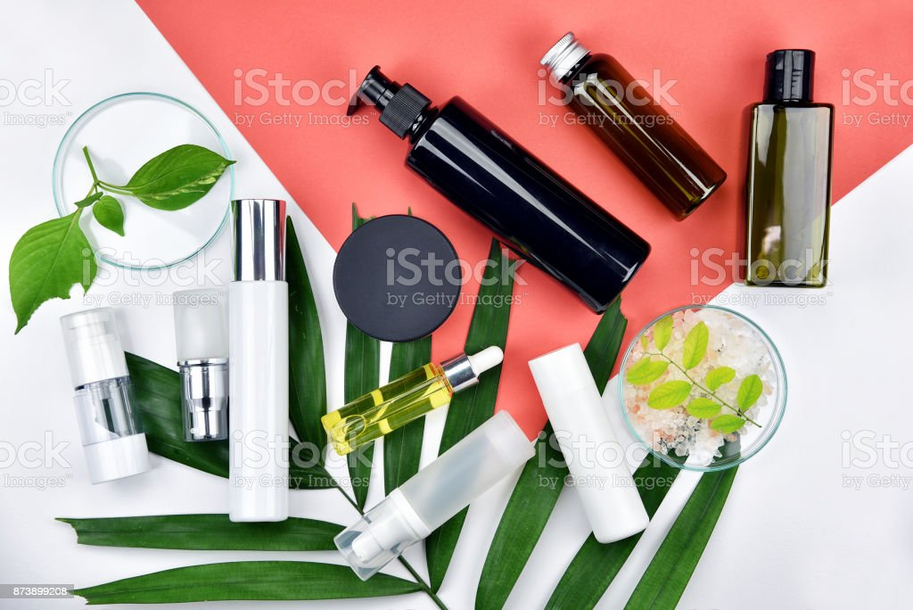 Cosmetic bottle containers with green herbal leaves, Blank label for branding mock-up, Natural beauty product concept, Flat lay on color background. stock photo