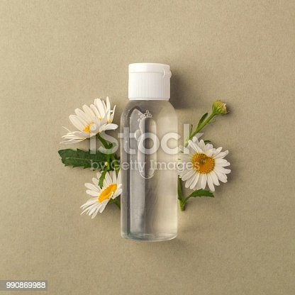 istock Cosmetic bottle containers with hermal camomile flowers Blank label for branding mock-up, Natural organic beauty product concept. 990869988