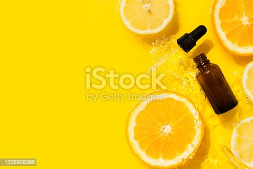 istock Cosmetic bottle product serum vitamin C with orange and lemon flat lay on yellow background clean water splashing 1226906085