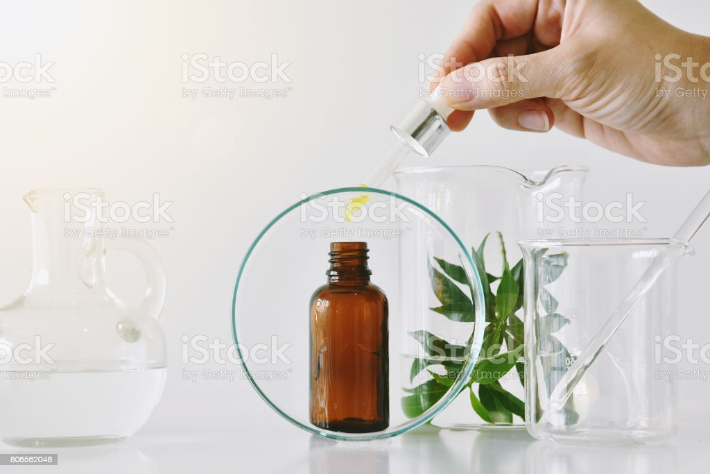 Cosmetic brown bottle containers  and scientific glassware, Focus on oil dropping in blank label package for branding mock-up stock photo