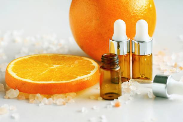 Cosmetic brown bottle containers with fresh orange slices, Blank label for branding mock-up, Natural Vitamin C beauty product concept. stock photo