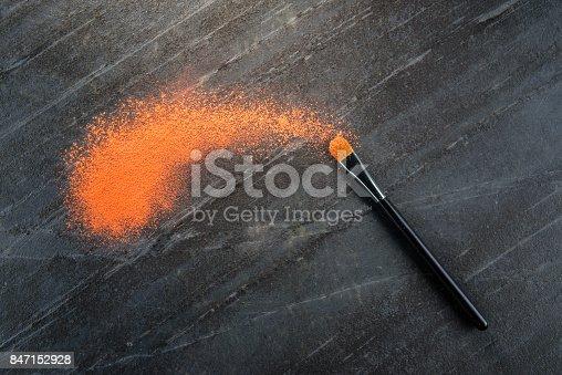 istock cosmetic brush tool touching orange crushed powder 847152928