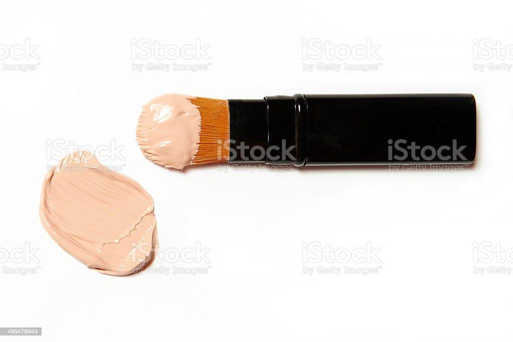Cepillo cosmético con smeared foundation sobre fondo blanco - foto de stock