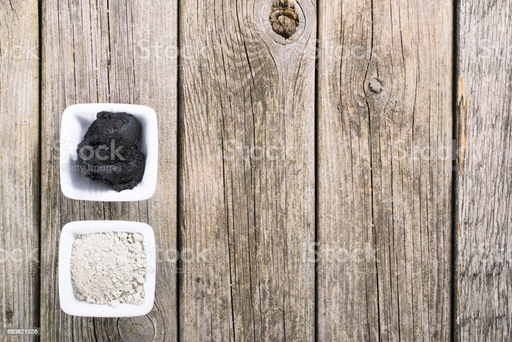 gray cosmetic clay powder and black mud on old wood texture