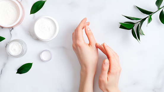 istock Cosmetic cream on female hands, jars with milk swirl cream and green leaves on white marble table. Flat lay, top view. Woman applying organic moisturizing hand cream. Hand skin care concept 1199860641