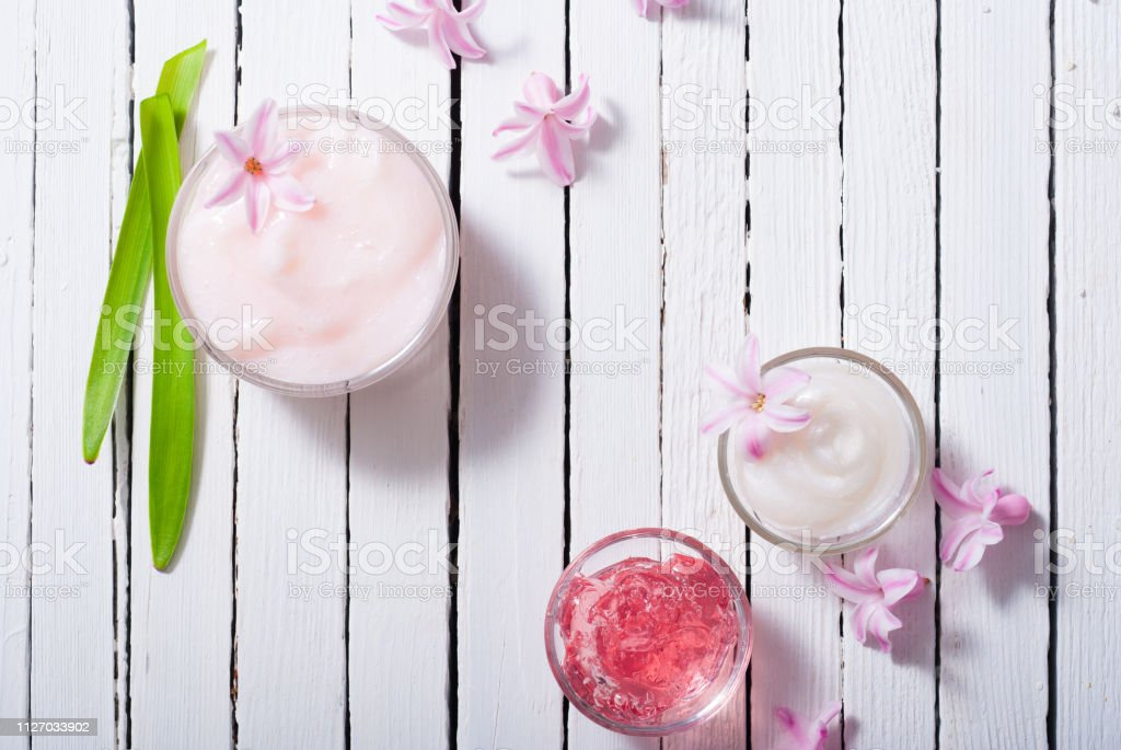 beauty products with hyacinth flowers on white wood
