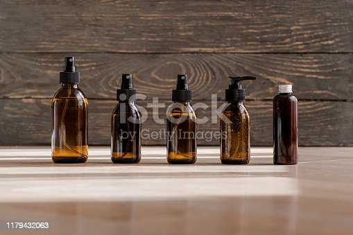 Cosmetic dark amber glass bottles on wooden background. Closeup, copyspace. Beauty blogging, salon treatment concept, miinmalism packaging