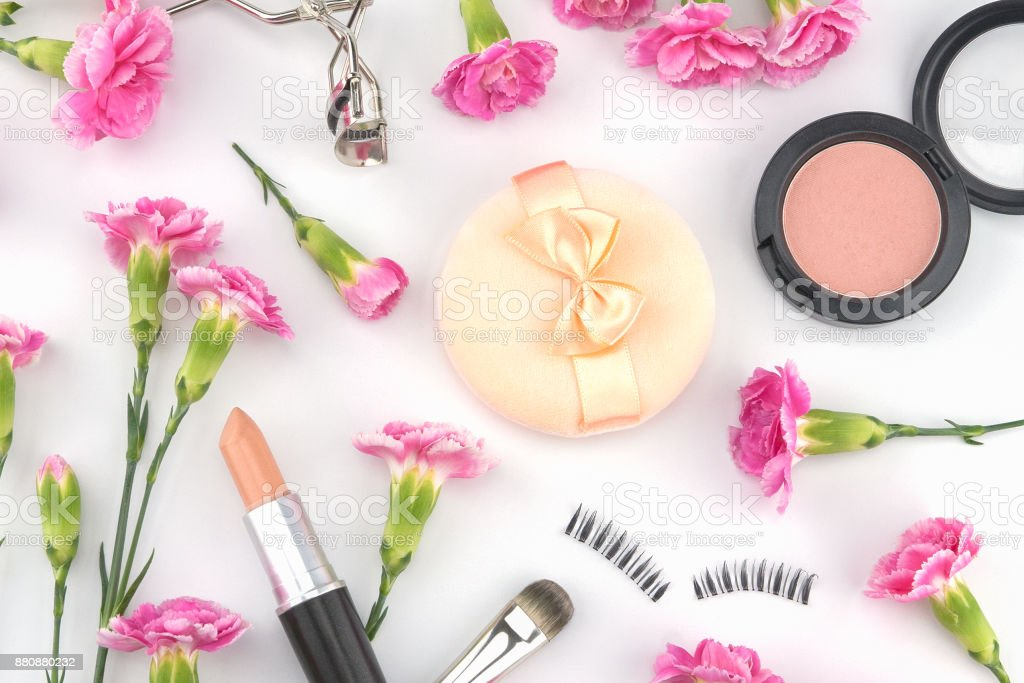 Cosmetic decorated with pink carnation flowers on white background stock photo