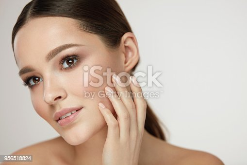 Cosmetic Face Care. Portrait Of Beautiful Girl Caressing Facial Skin Posing On Grey Background. Closeup Of Sexy Young Woman With Soft Clean Skin And Natural Makeup. Beauty Concept. High Resolution