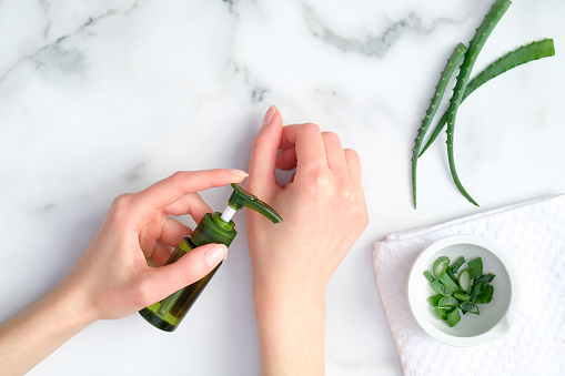 1151624350 istock photo Cosmetic lotion bottle on female hands and green sliced stems aloe vera on white marble table. Woman applying organic moisturizing hand cream. Hand skin care concept 1213818125