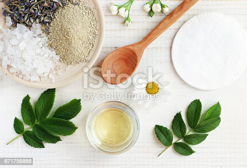 istock Cosmetic oil, clay, sea salt, herbs, plant leaves. Facial treatment preparation background. 671756888