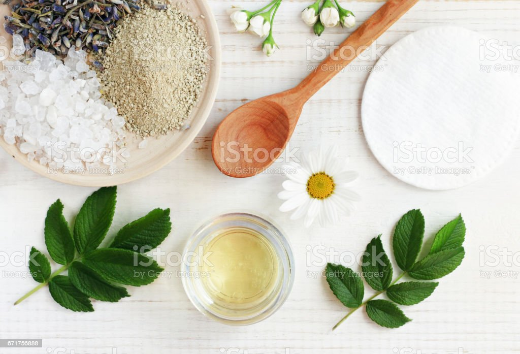 Cosmetic oil, clay, sea salt, herbs, plant leaves. Facial treatment preparation background. stock photo