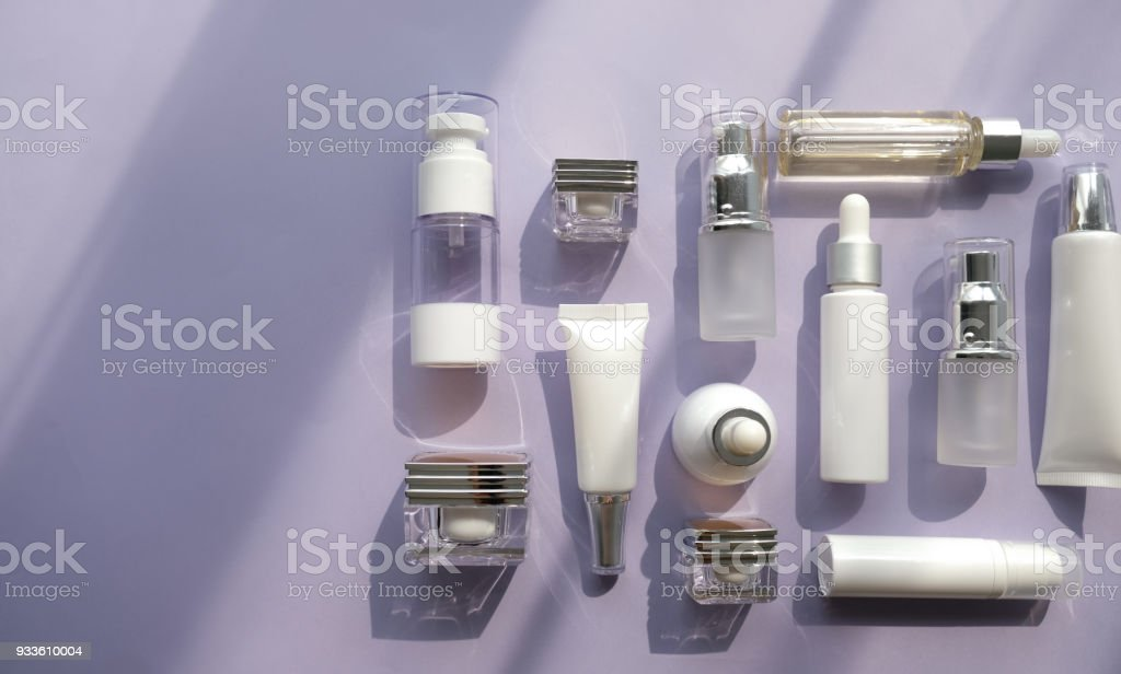 cosmetic packaging set on purple background. group of skincare cream serum oil . facial beauty cosmetic spa product. natural cosmetology concept skin treatment with green leaf and laboratory science glassware. royalty-free stock photo