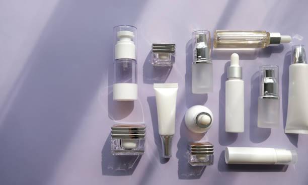 化粧品の包装は、紫色の背景に設定します。スキンケア クリーム血清オイルのグループ。顔の美容化粧品スパ製品。緑葉研究所科学ガラスと自然美容概念の肌の治療。 ストックフォト