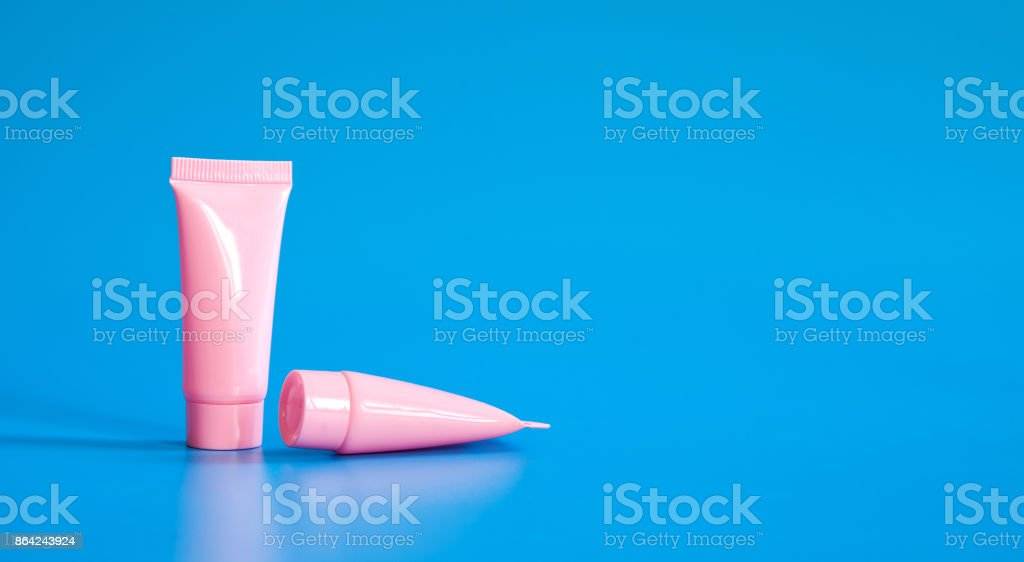 Cosmetic tubes on blue background. Abstract cosmetic cleaning...