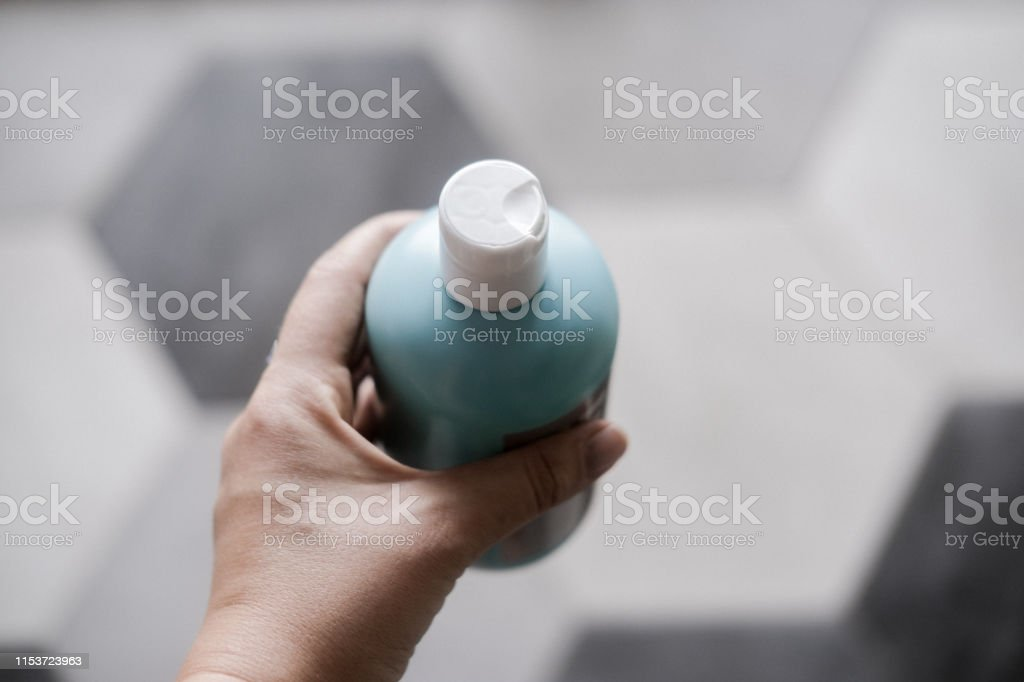 Cosmetic plastic bottle in blue color on gray - Foto stock royalty-free di Adulto